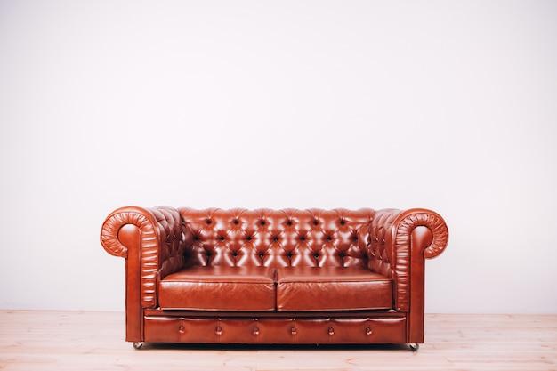 Canapé en cuir marron sur une lumière. canapé en cuir avec boutons. canapé en cuir au bureau.