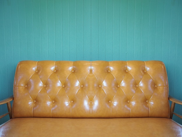 Canapé en cuir marron avec panneau en bois de couleur vintage.