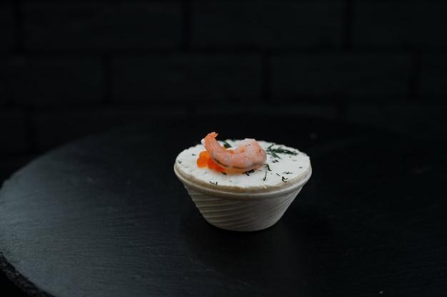 Un canape avec du pâté et des crevettes avec des verts se dresse dans une assiette blanche sur une table noire dans un restaurant. délicieuse délicatesse de fruits de mer