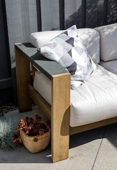Canapé d'extérieur en bois avec coussins blancs