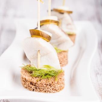 Canapé de hareng avec oignon, concombre mariné et aneth