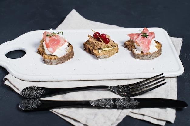 Canape avec jambon, salami et pâté de canard sur une planche à découper blanche