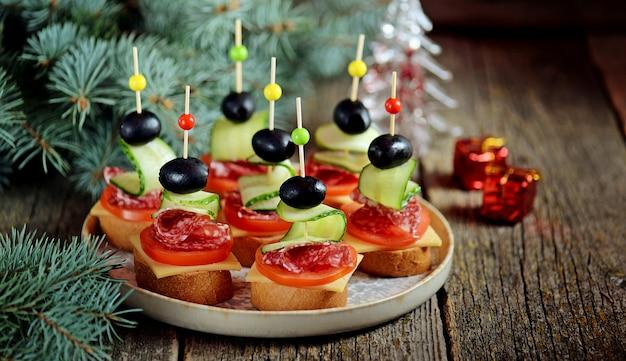 Canape de noël sur brochette de pain baguette avec pain grillé, saucisse, tomate, concombre et olives.