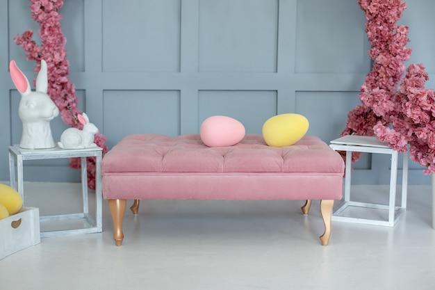 Canapé rose clair et décoration de pâques dans une chambre avec des fleurs roses autour
