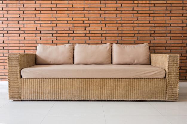 Canapé en rotin avec coussins gris et fond de mur de brique rouge