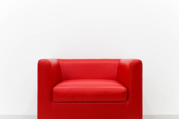 Le canapé rouge de meubles est situé à côté du mur de ciment blanc.