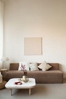 Canapé, table basse avec décorations, lampe, cadre photo vierge sur le mur.