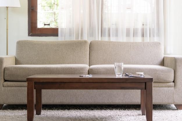 Canapé vide avec de l'eau et des comprimés de médicaments sur la table