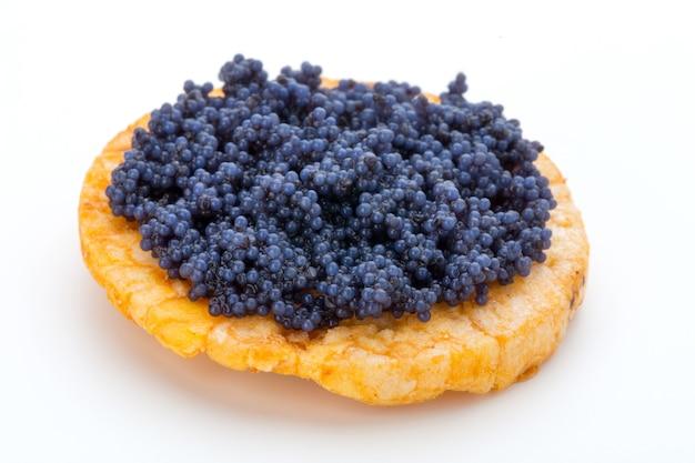 Canapés au caviar d'esturgeon noir sur blanc isolé.