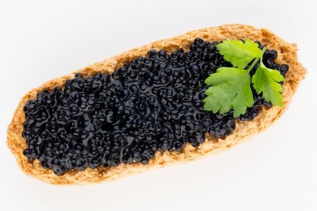 Canapés au caviar d'esturgeon noir et épices isolés sur le blanc