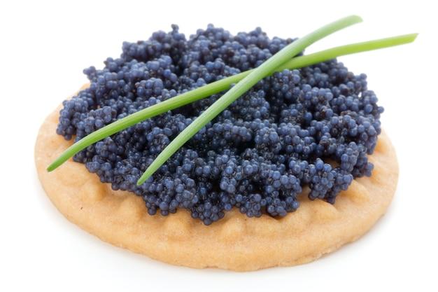 Canapés au caviar d'esturgeon noir et épices isolés sur la surface blanche.