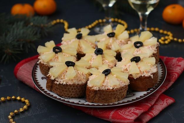 Canapés au fromage à la crème, bâtonnets de crabe, olives noires et ananas