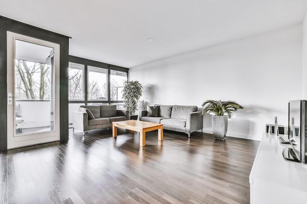 Des canapés confortables et une table en bois placée près de plantes en pot contre la fenêtre dans le salon de l'appartement moderne