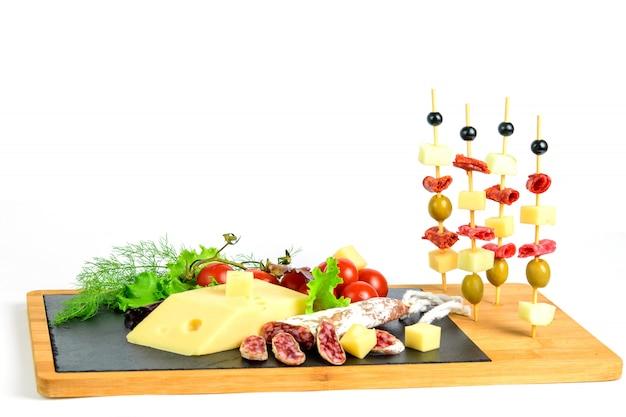 Canapés de tranches de fromage, chorizo, salami, olives et pomme sur la planche à tapas en bois. espace.
