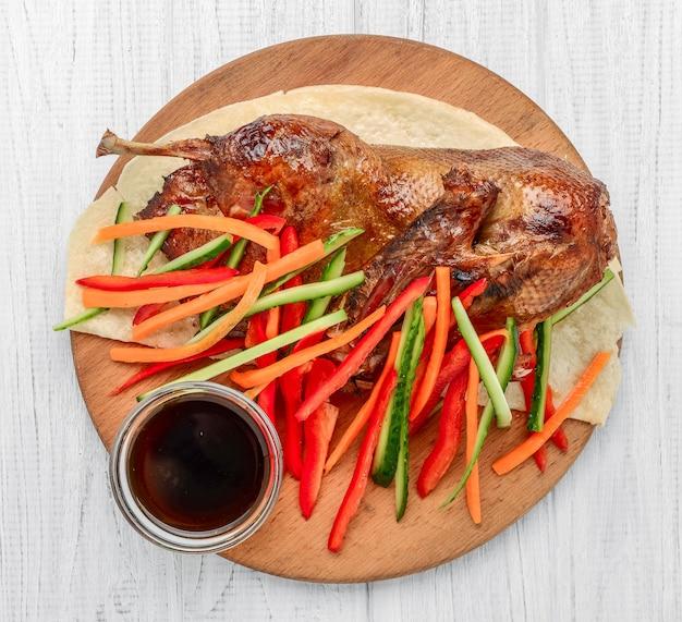 Canard au four avec des légumes sur une surface en bois