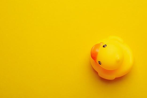 Canard en caoutchouc sur fond jaune, espace pour le texte