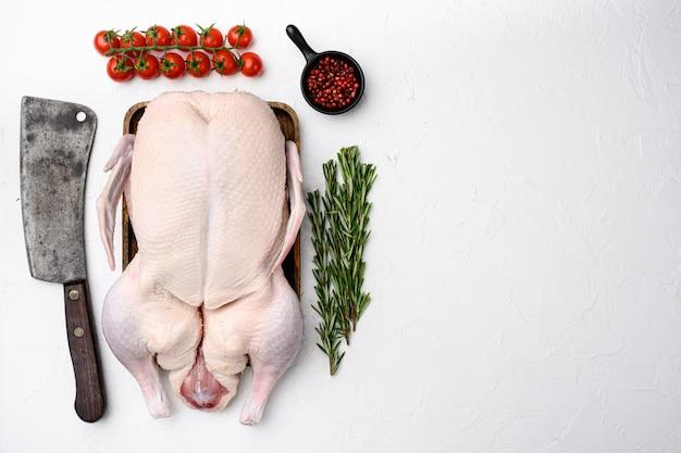 Canard entier cru frais prêt pour la cuisson avec des herbes, sur fond de table en pierre blanche, vue de dessus à plat, avec espace de copie pour le texte