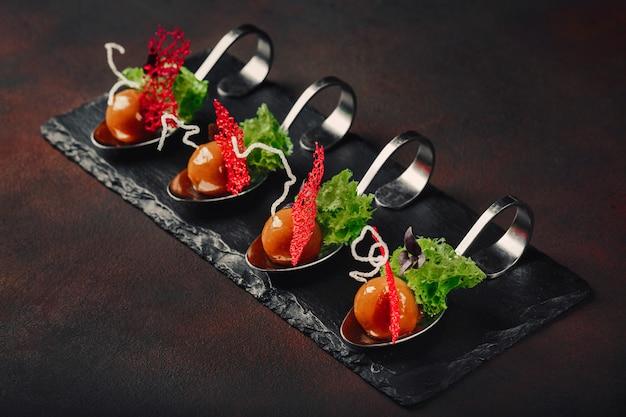 Canard galantine de cuisine moderne moléculaire en cuillères sur fond de pierre et rouillé