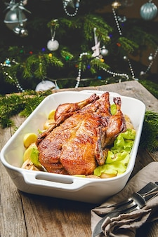Canard de noël avec des pommes et des herbes dans une casserole blanche avec des décorations de vacances d'hiver