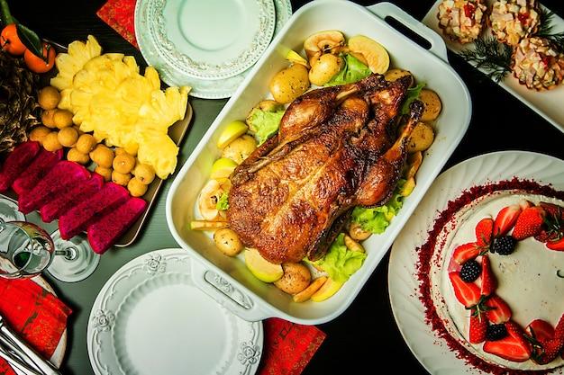 Canard de noël avec des pommes et des herbes dans une casserole blanche sur fond de bois, vue du dessus
