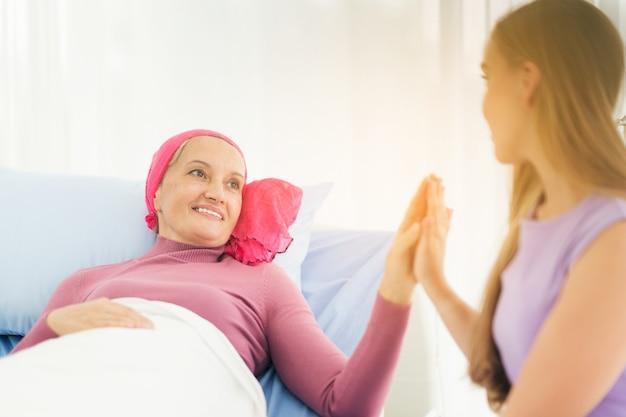 Cancer femme couchée soutenue par maman à la maison.