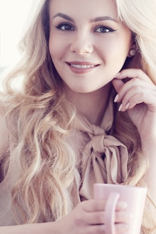 Candide belle femme blonde portrait avec thé ou café rose tasse
