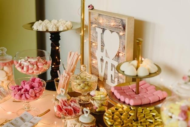 Candy bar joliment décoré avec des bonbons lors d'un événement vintage.