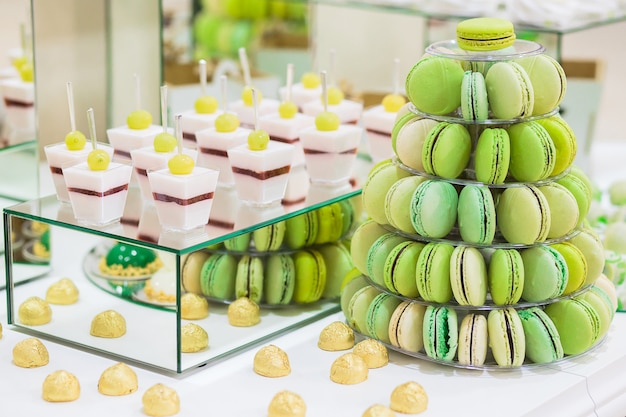 Candy bar avec macarons, gâteaux, cheesecakes, cake pops. pyramide de macarons verts colorés.
