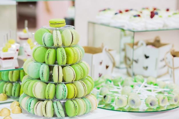 Candy bar avec macarons, gâteaux, cheesecakes, cake pops, pyramide de macarons verts.