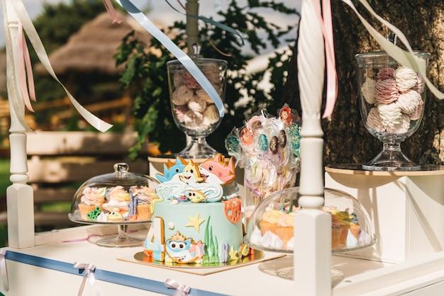 Candy bar pour votre anniversaire. fête d'enfants aux couleurs pastel dans la nature. beau gâteau sucré, guimauves à la main, cupcakes, sucettes, meringues.