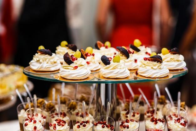 Candy bar. table avec différents bonbons pour la fête. table à dessert pour la fête de mariage. décoré délicieux. bonbons, bonbons, desserts, cupcakes, tartelettes, macarons, gâteaux et muffins.