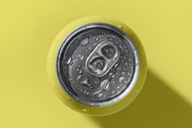 Canette de boisson gazeuse jaune avec des gouttes d'eau projetant l'ombre