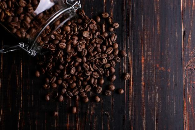 Une canette de café, des grains épars sur une table en bois.