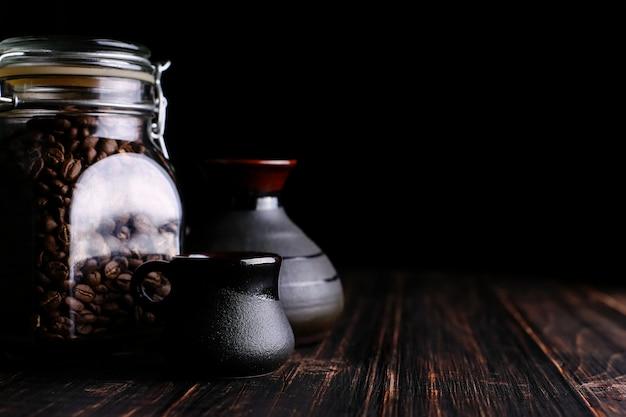 Une canette de café, une tasse et un turk sur une table en bois, sur un fond noir.
