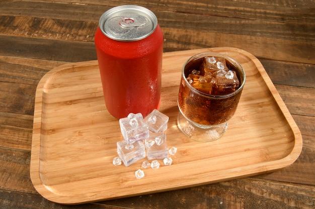 Canette de soda avec un verre plein de glace et boire sur un plateau en bambou