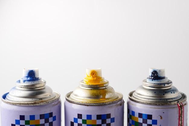 Canettes usagées de peinture en aérosol sur fond blanc