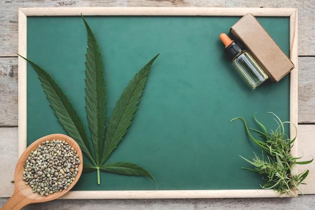 Cannabis, graines de cannabis, feuilles de cannabis, huile de cannabis placé sur un tableau vert sur un plancher en bois.