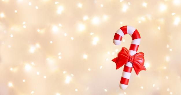 Une canne en bonbon bonbons de noël à rayures rouges et blanches sur fond de guirlande de lumières