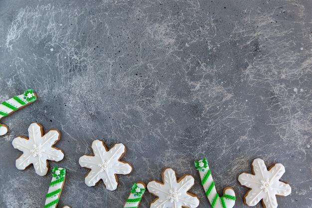 Canne en bonbon et flocons de neige verts et blancs de pain d'épice de noël peints à la main sur un beau fond gris.