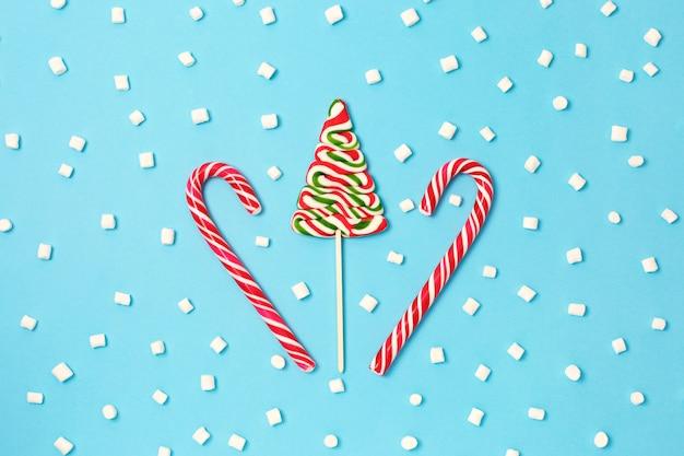 Canne en bonbon de noël et arbre de noël avec des guimauves sur fond bleu.