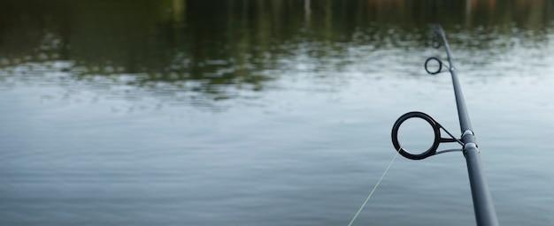 Canne à pêche au-dessus de l'eau douce avec bannière d'espace de copie