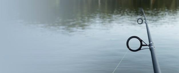 Canne à pêche au-dessus de l'eau du lac avec espace de copie pour la bannière de texte