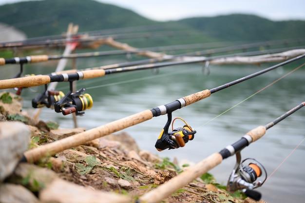 La canne à pêche du pêcheur repose sur le bord du lac.