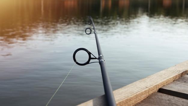 Canne à pêche sur l'eau du lac allongé sur la jetée en bois