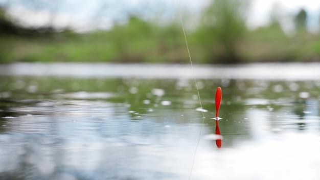 La canne à pêche flotte dans l'eau.