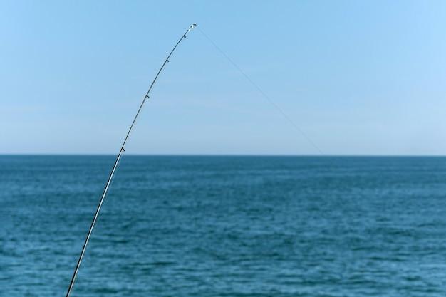 Canne à pêche sur fond bleu océan ou mer, espace copie. en attendant le plus gros coup. sport relaxant méditatif.