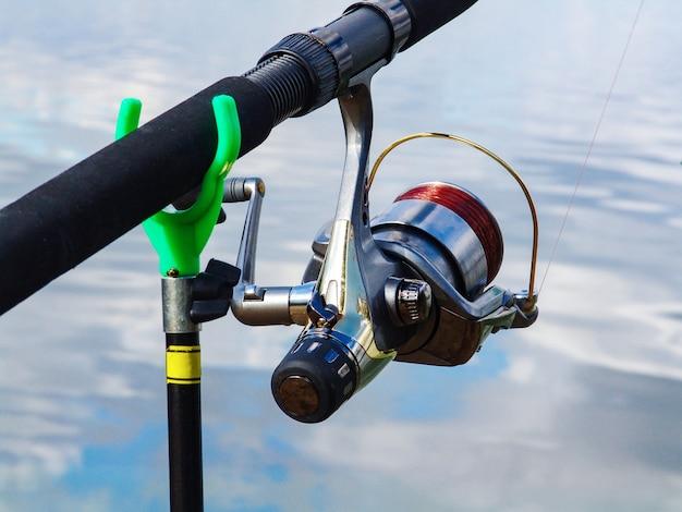 Canne à pêche sur le support et bobine avec le gros plan de ligne de pêche