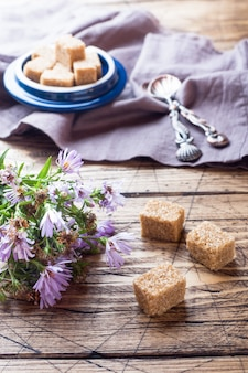 Canne à sucre brune et un bouquet de fleurs sur une table en bois.