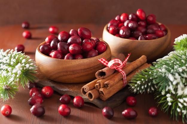Canneberge fraîche dans des bols en bois, décoration d'hiver