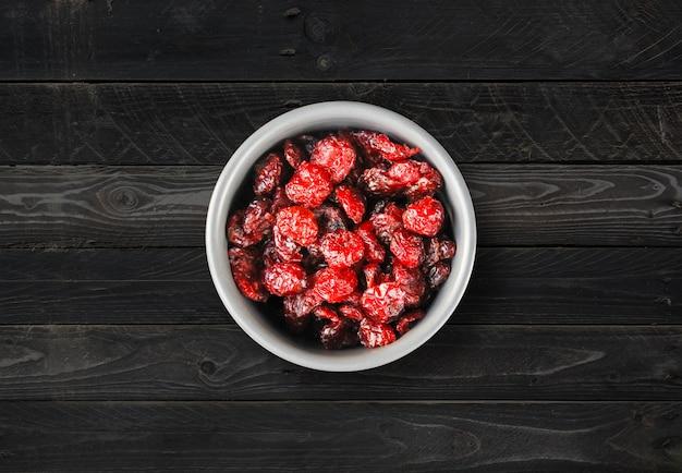 Canneberges dans un bol sur une table de cuisine. fond de bois noir. vue de dessus